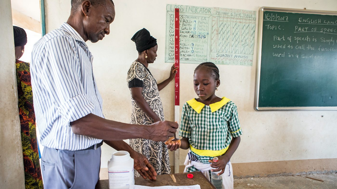 A health worker gives a schoolgirl a tablet to protect against intestinal worms.