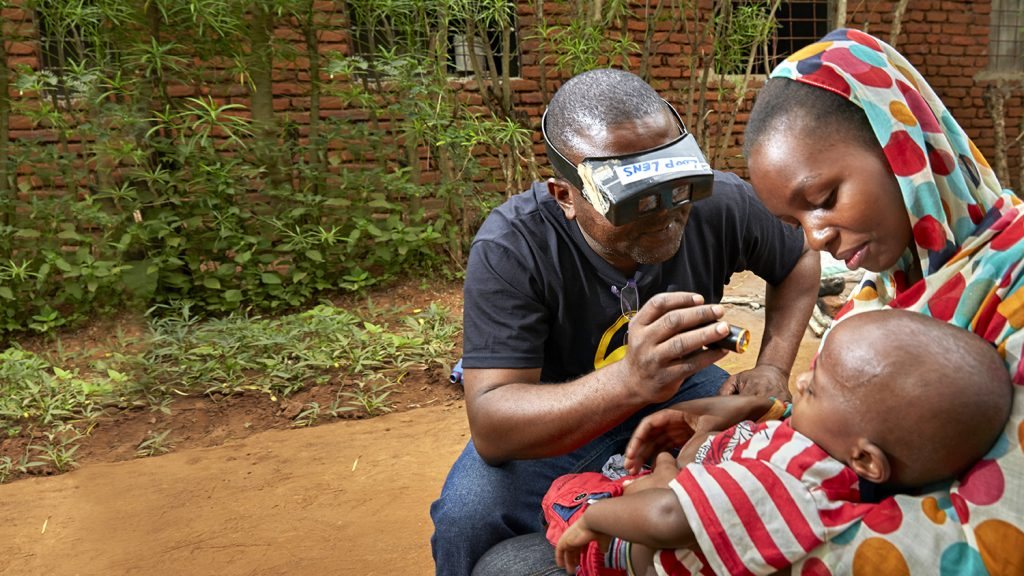 Toddler Baraka has his eyes checked by a health worker.