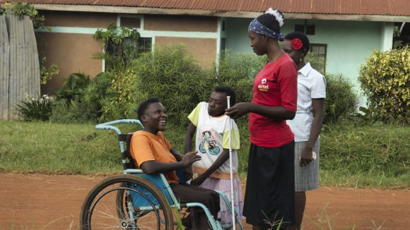 Four women chatting on a dirt road in Uganda. One uses a white cane, one has restricted growth and one uses a wheelchair.