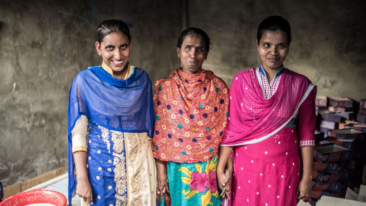 Three women standing side by side and smiling.