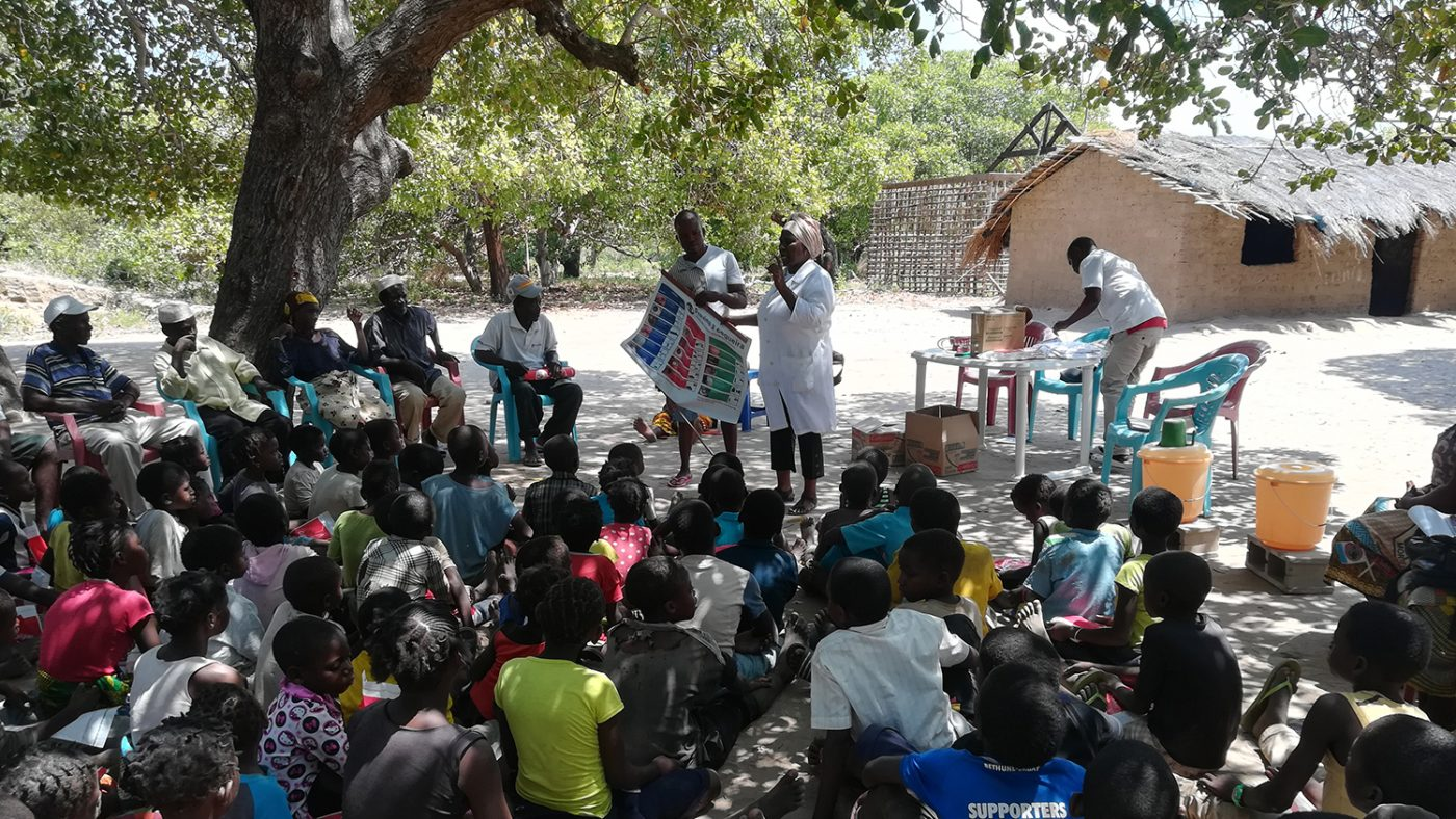 Women teaching children outside under a tree.