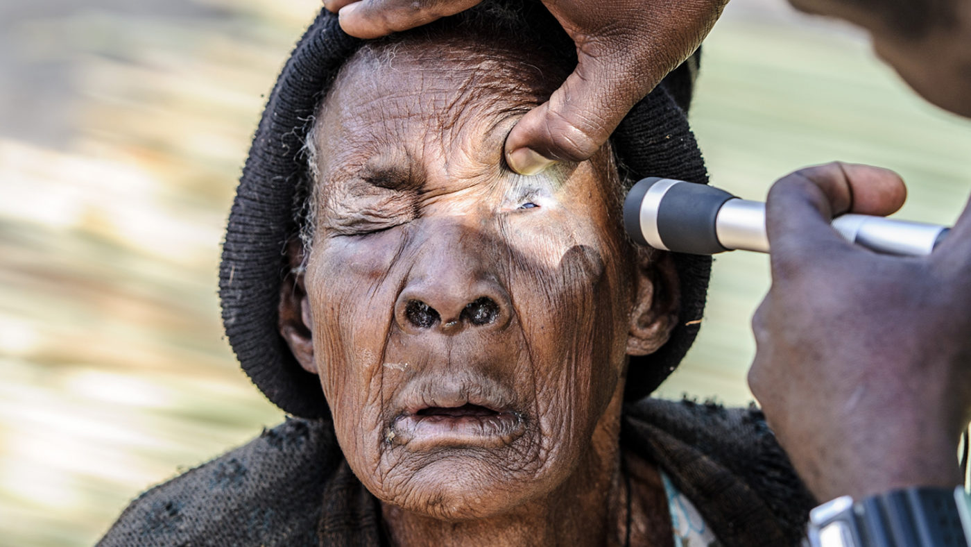 A woman has her eyes examined by a health worker, who shines a torch into her eye.