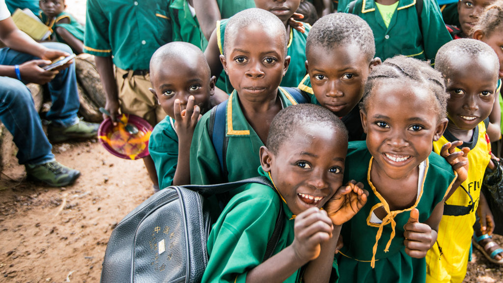 School children in Sierra Leone smile at the camera.