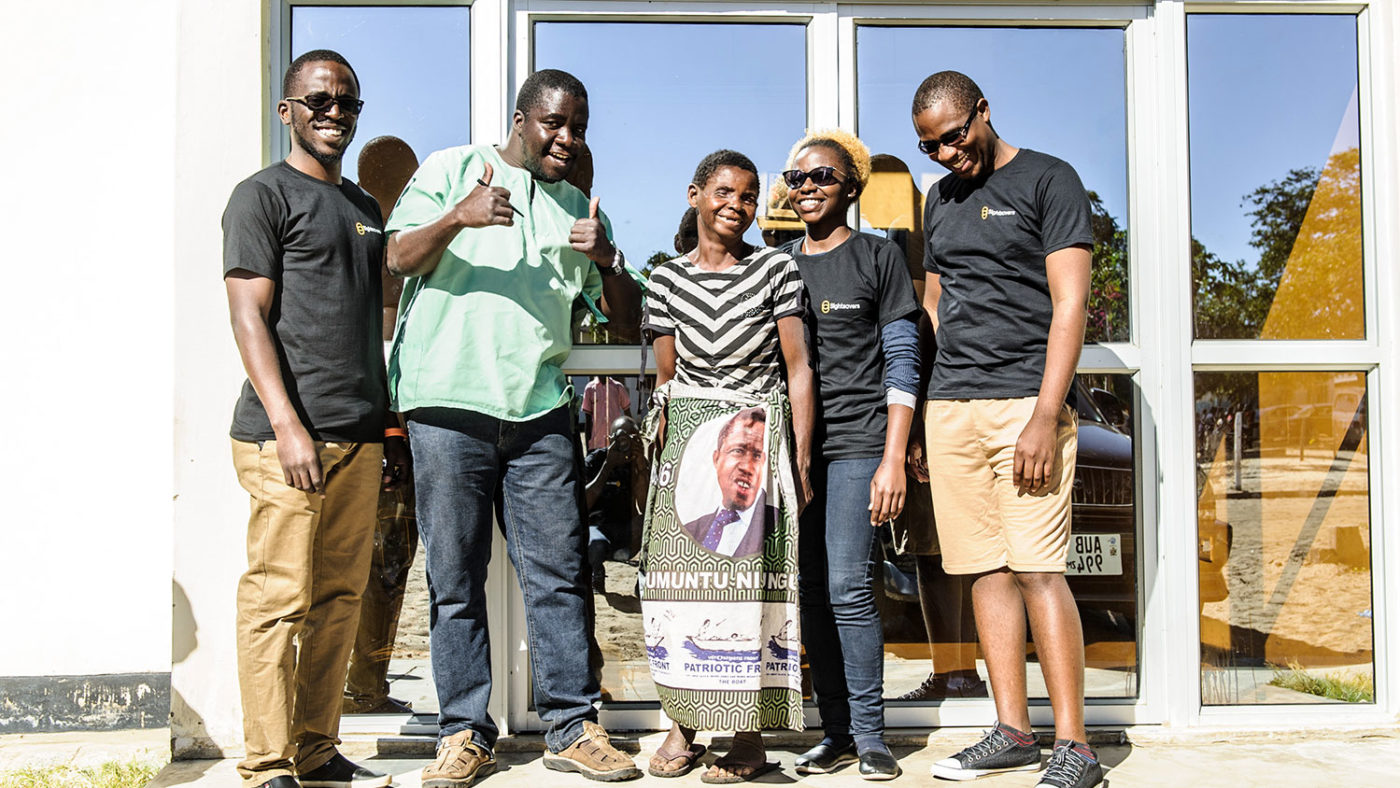 Mariah, Mr Ndalela and other Sightsavers members of staff stand outside Senanga General Hospital following Mariah's operation.