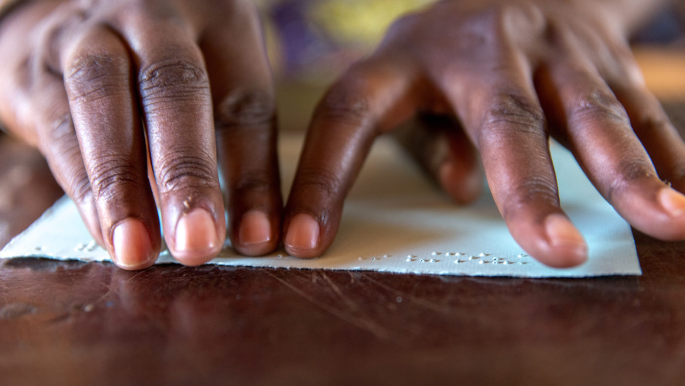 Close-up of hands reading braille.