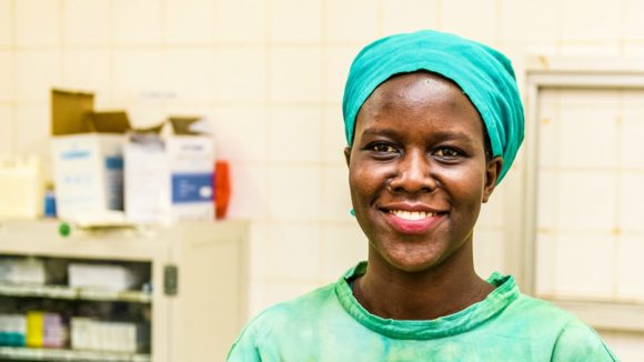 Gladys Atoo in her Doctor's uniform, smiles at the camera