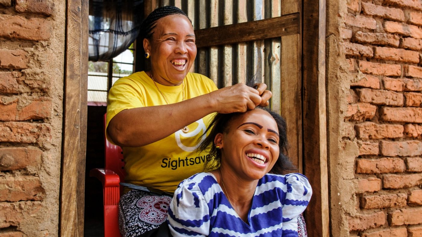 Halima is braiding the hair of one of her family members