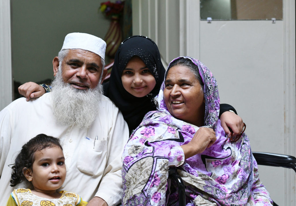 Naheed smiles at home surrounded by her family