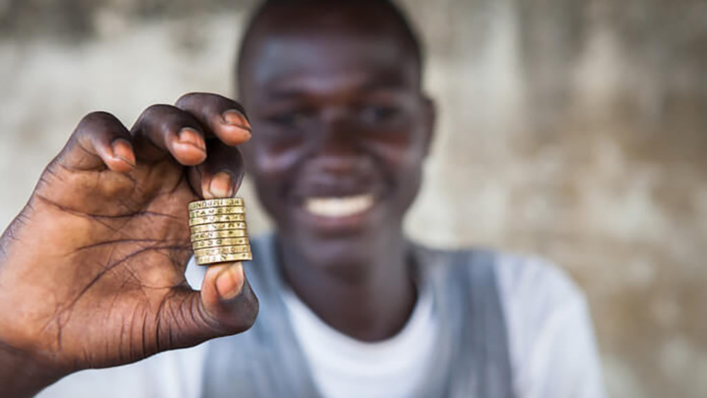 A boy holding a stack of coins.