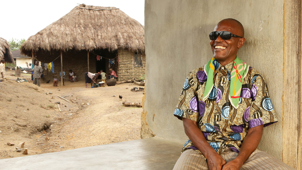 A man wearing sunglasses sits outside a hut in his village, smiling broadly.