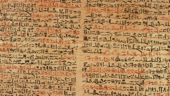 An ancient Egyptian papyrus, showing writing in red and black ink.