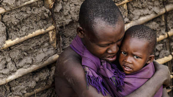Aluna holds Bibie outside their house in Tanzania.