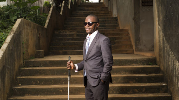 Floreal Serge Adieme wearing dark glasses and holding a white cane.