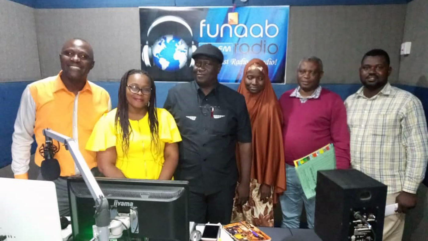 A group of people stand in a radio studio in Nigeria.