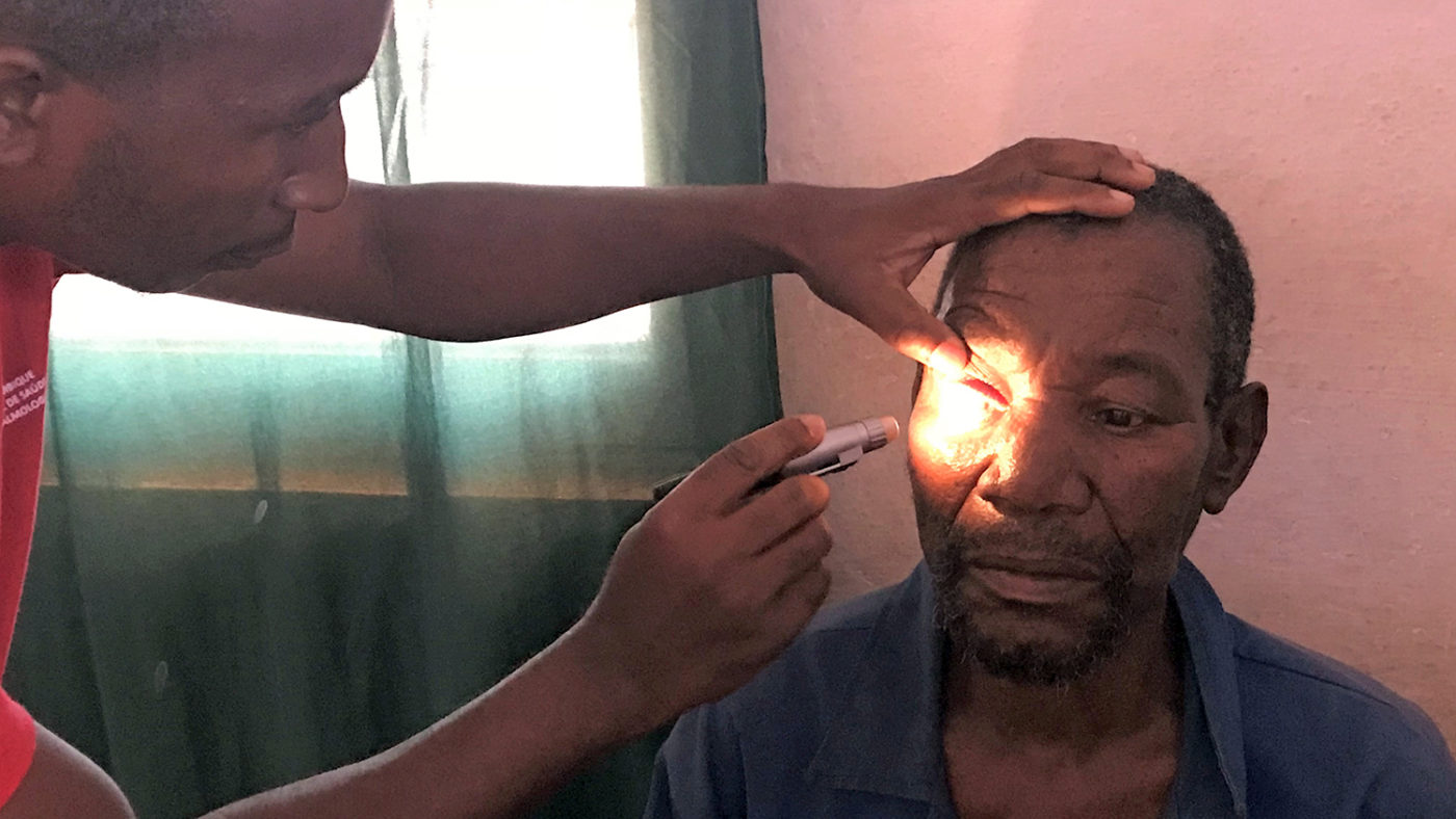An eye health worker shines a light into Poligarpo's eyes to check for cataracts.