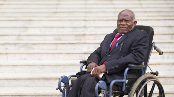 Senator Robert Oyono in his wheelchair in front of some steps.