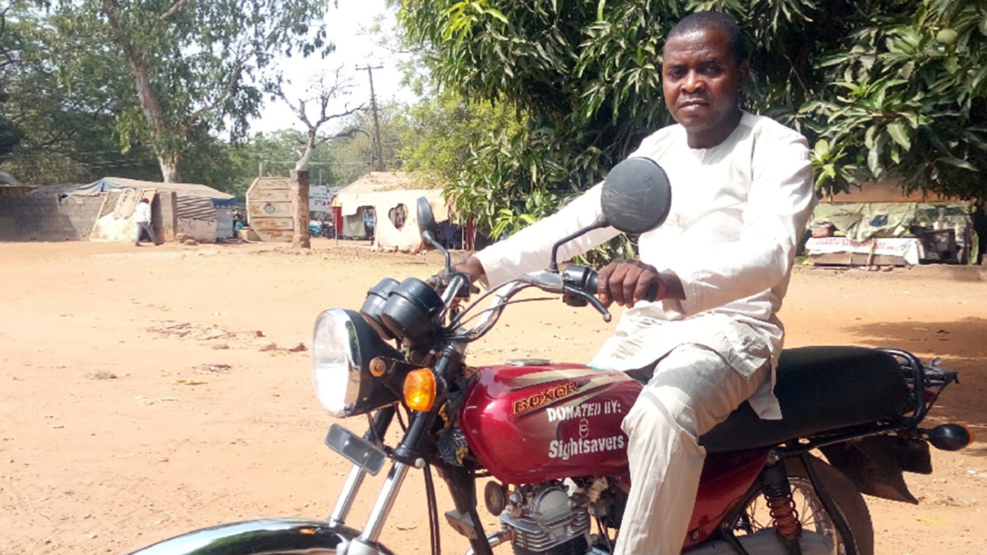 An eye health worker sits on a new motorbike.
