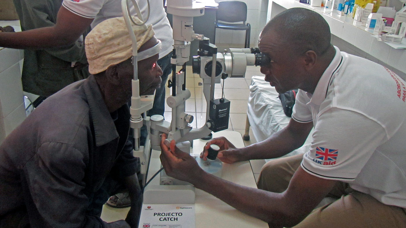 A patient has his eyes checked by a health worker.