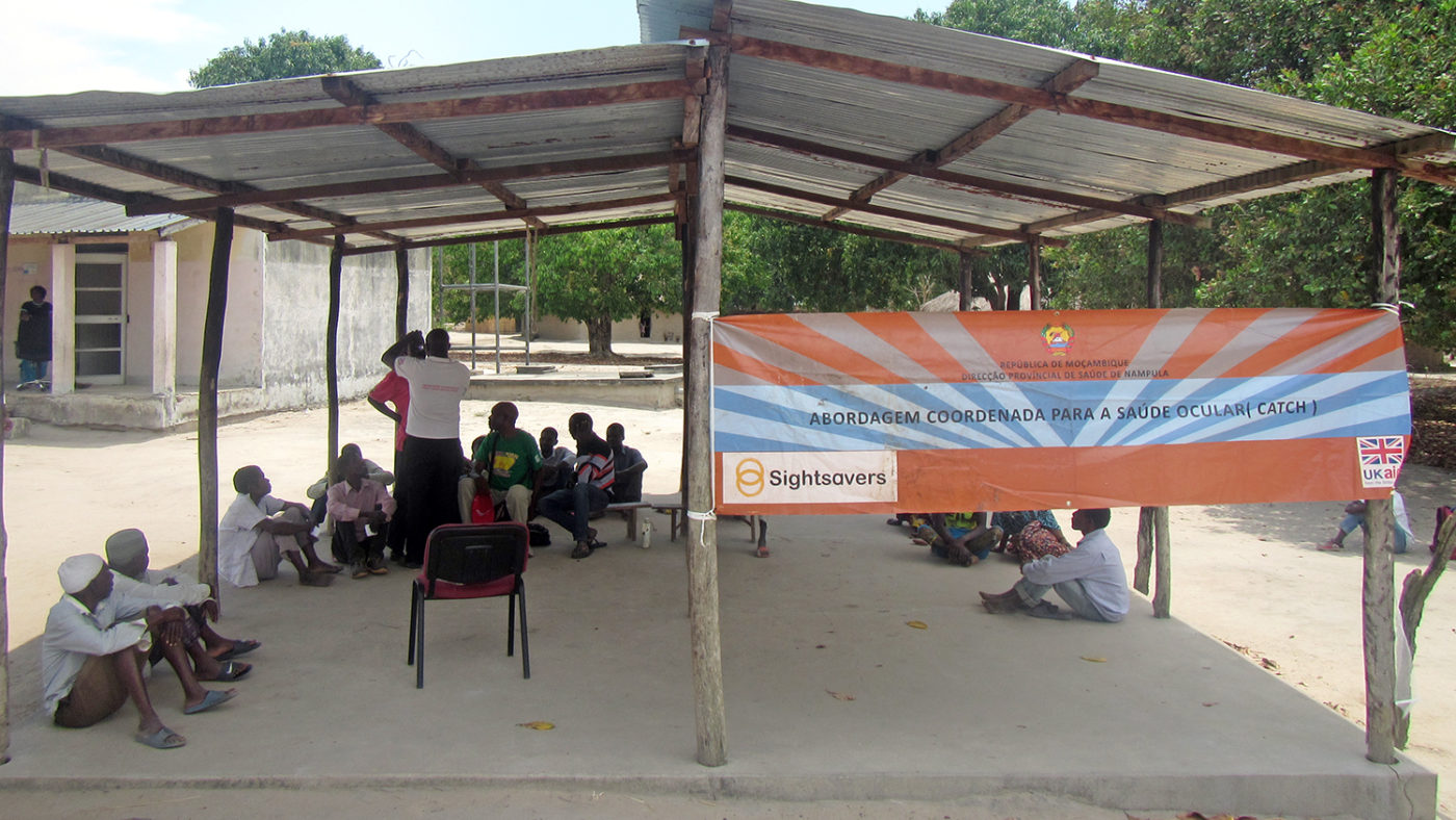 A temporary structure with people sitting underneath, with a sign featuring the Sightsavers logo.