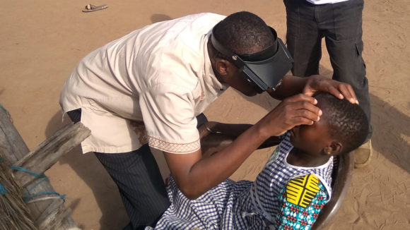 A volunteer in Cote d'Ivoire learns how to spot trachoma by examining a child's eyes.