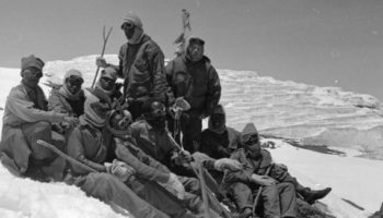 Old black and white photo showing a group of young men on a mountain slope.