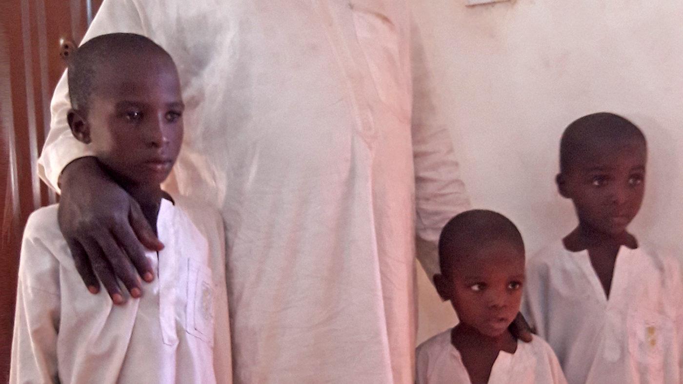 Three young boys wearing white smocks.