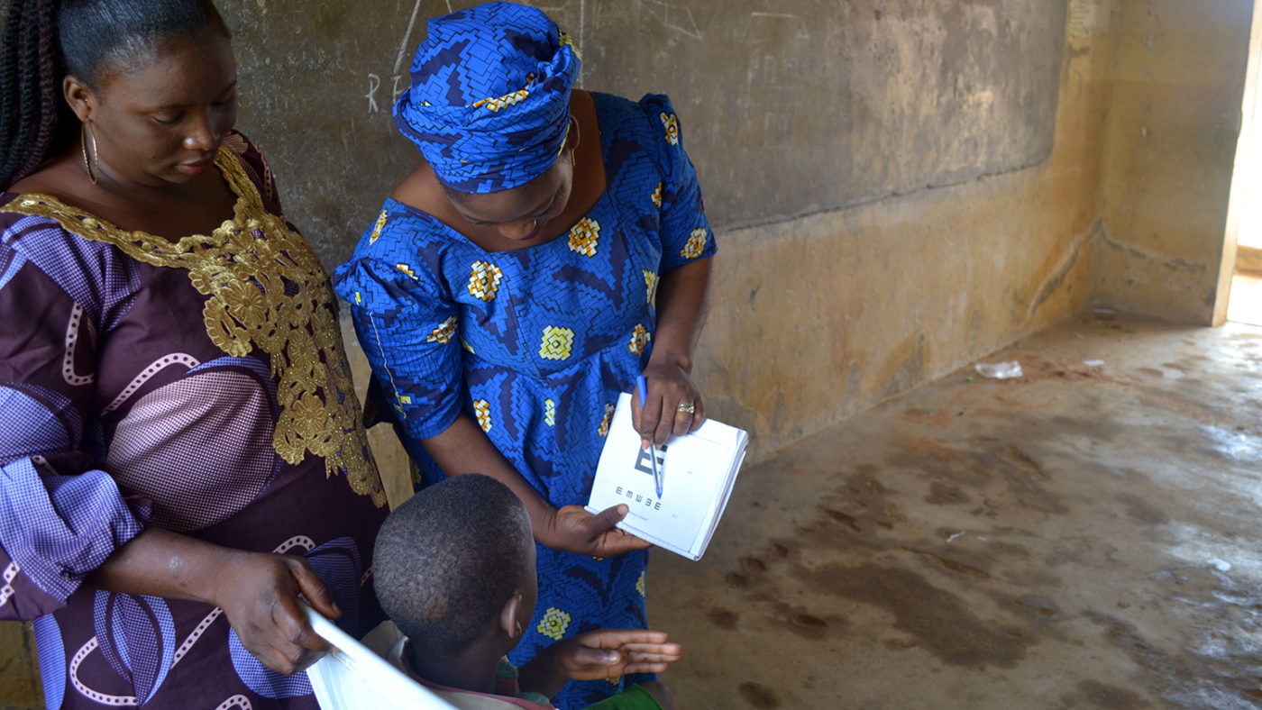 Rakiya shows a student a page from her eye test book.