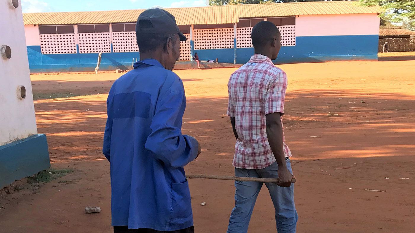 Poligarpo's nephew uses a stick to guide him around the village.