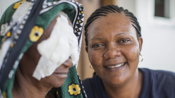 An eye care worker smiles at the camera next to a woman with bandages on her eyes.
