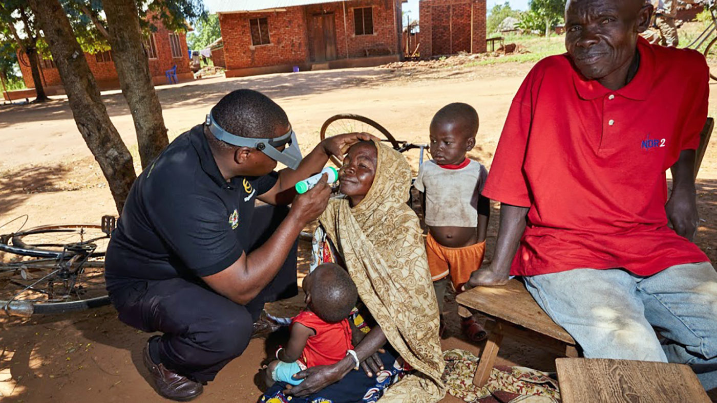An eye health worker examines a woman's eyes, with her family gathered round her.