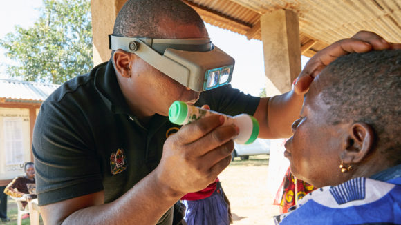 An eye health worker examines a woman's eyes to check for signs of trachoma.