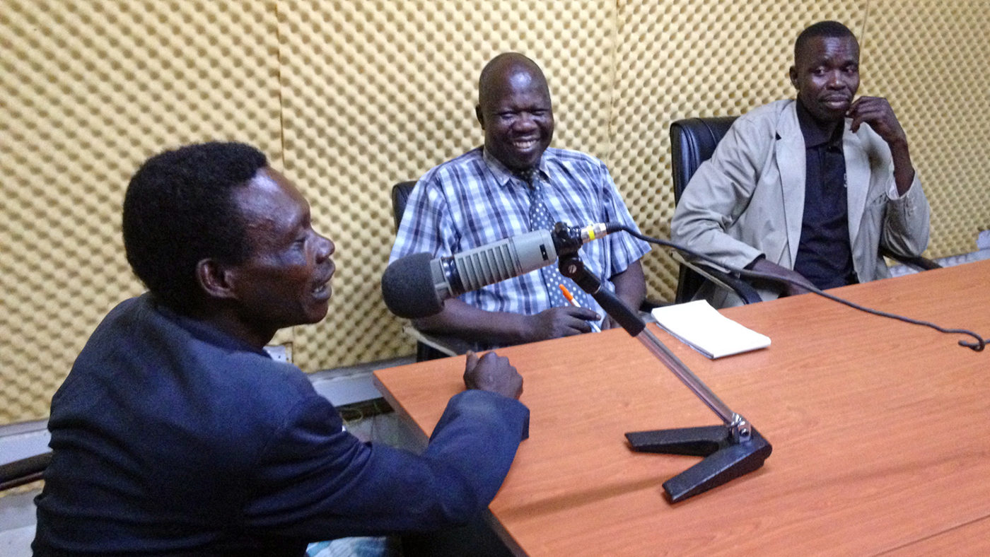 A man speaks into a microphone at a radio studio in Uganda.