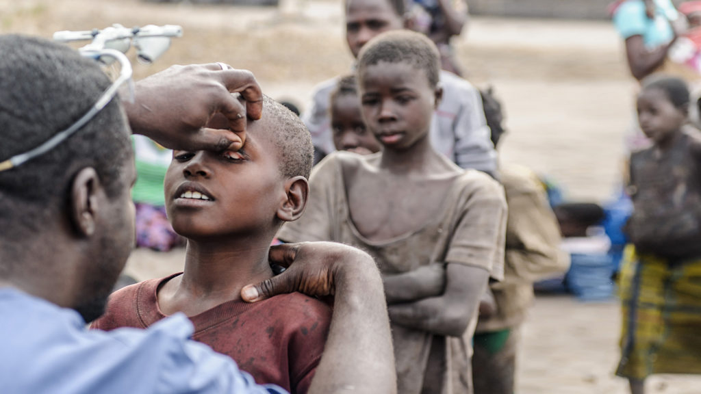 Eye surgeon Dr Ndalela examines a child's eyes to check for signs of trachoma.