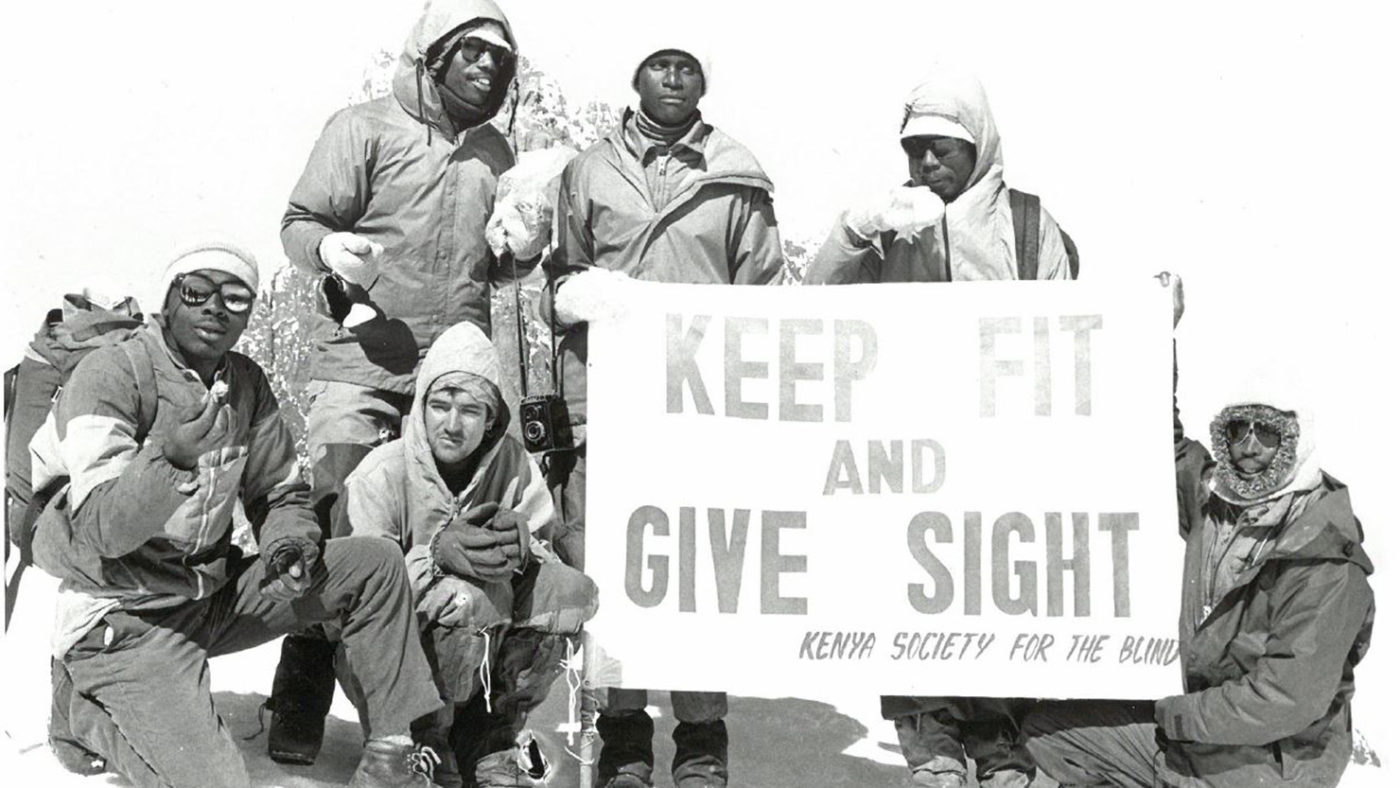 Old black and white photo showing a group of men in cold weather mountaineering clothing holding a sign saying 'Keep fit and give sight'.