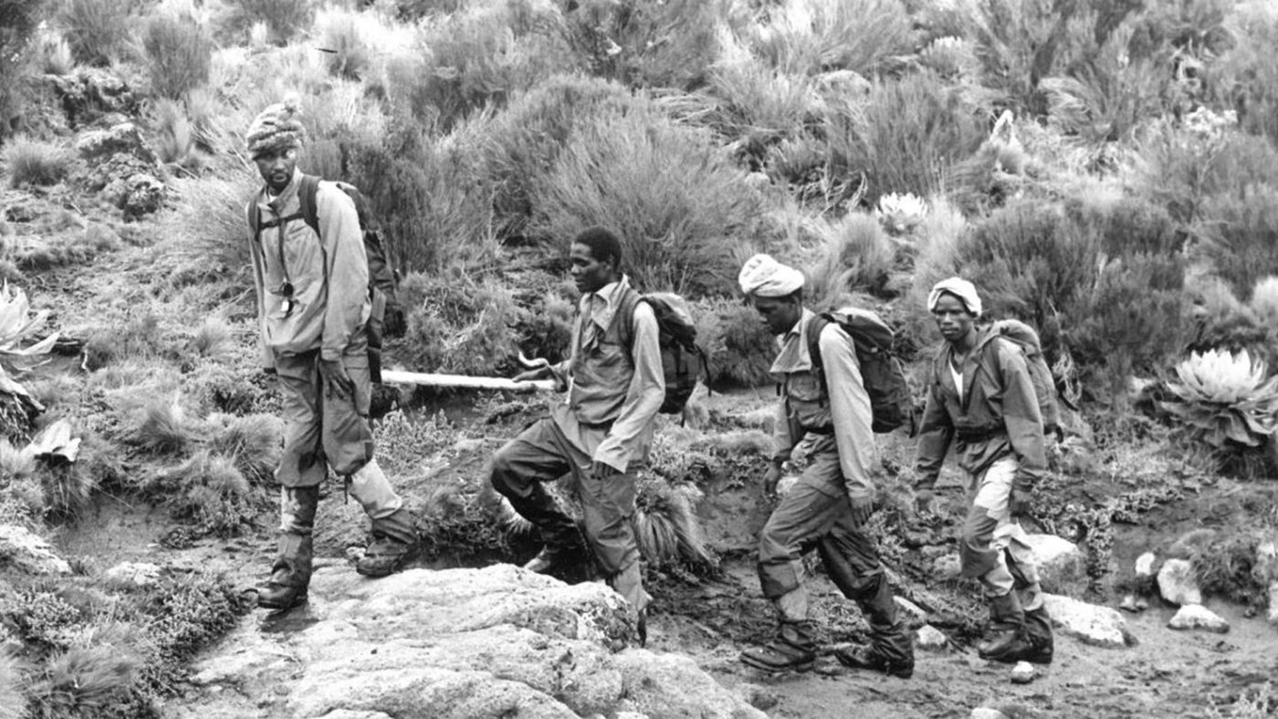 An old black and white photo showing four men training for a climb in rugged bushland.