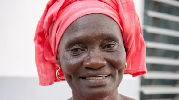 A woman in a pink headscarf smiling at the camera.