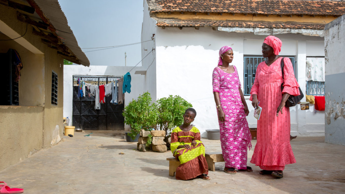 Outside in the courtyard of some single-storey dwellings, two women stand together, and a young girl sits next to them.