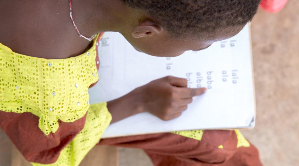 A young girl reading a school exercise book.