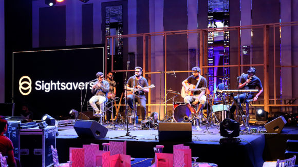 A group of musicians play guitar on stage, with Sightsavers banners in the background.