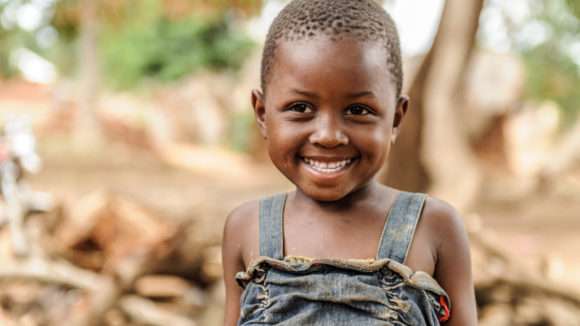 Filly, a little girl from Tanzania smiles at the camera. She has trachoma.