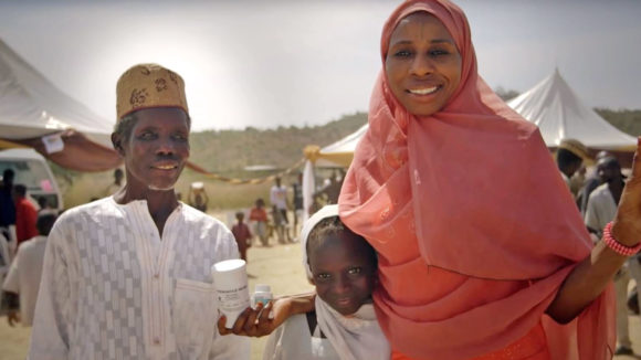 A still from Sightsavers' video, showing a smiling man, woman and child.