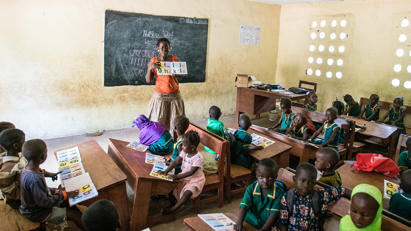A teacher stands at the front of the class in Sierra Leone.