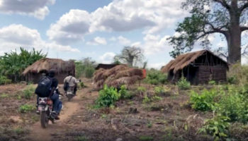 An eye health team on motorbikes travel across a dusty remote landscape dotted with trees and huts.