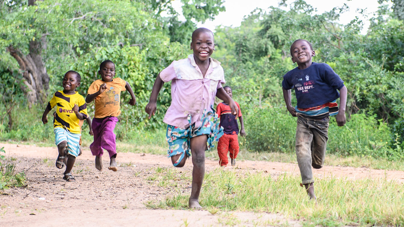 A group of children smile and run through their village.