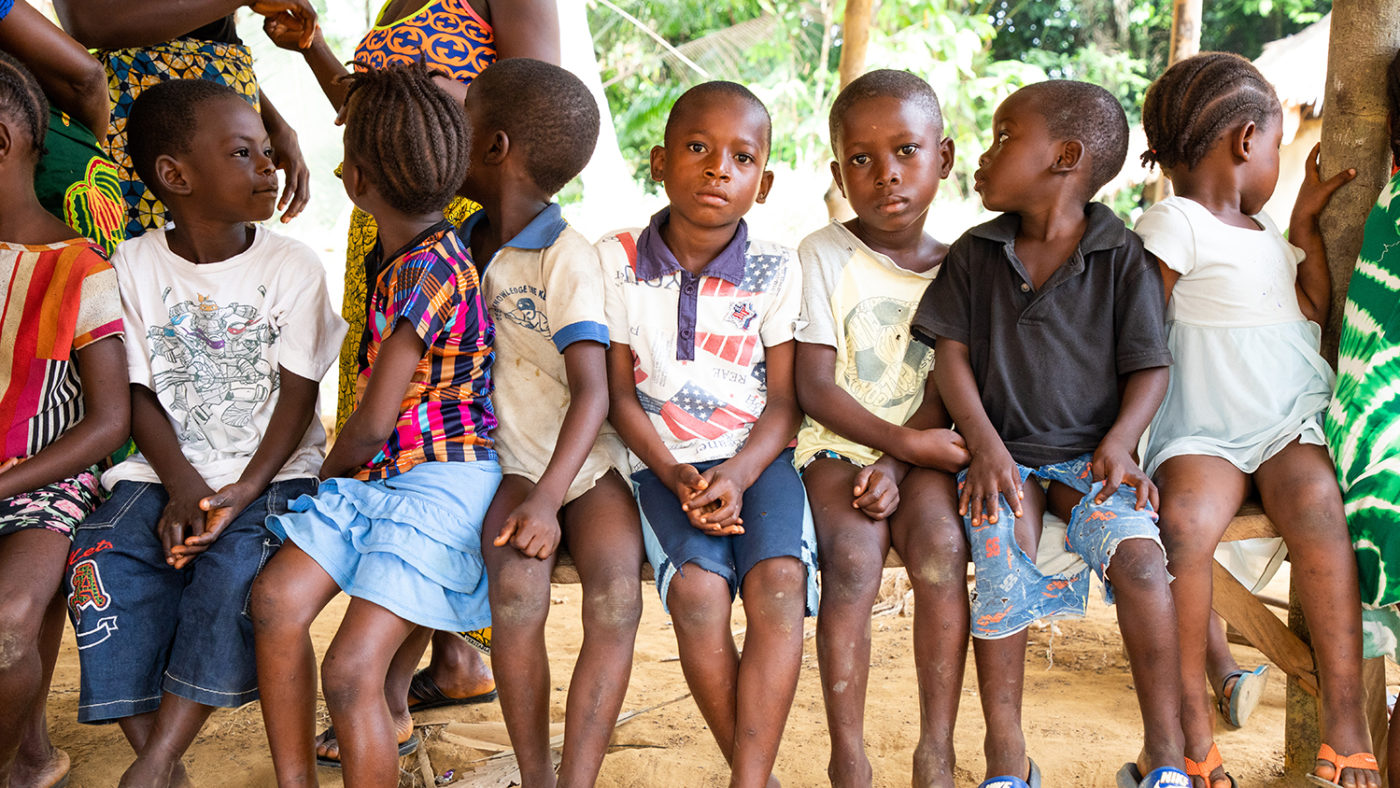 A group of children sit in a line on a bench waiting to be tested for river blindness.