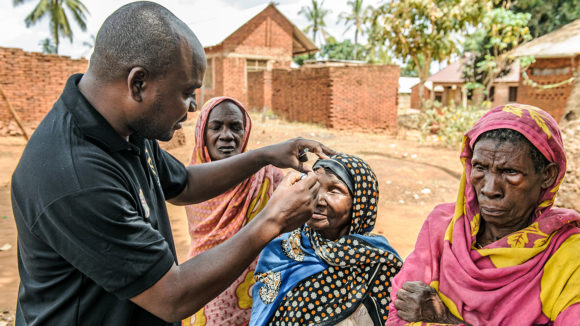 An eye surgeon examines a woman's eyes to check for signs of trachoma.