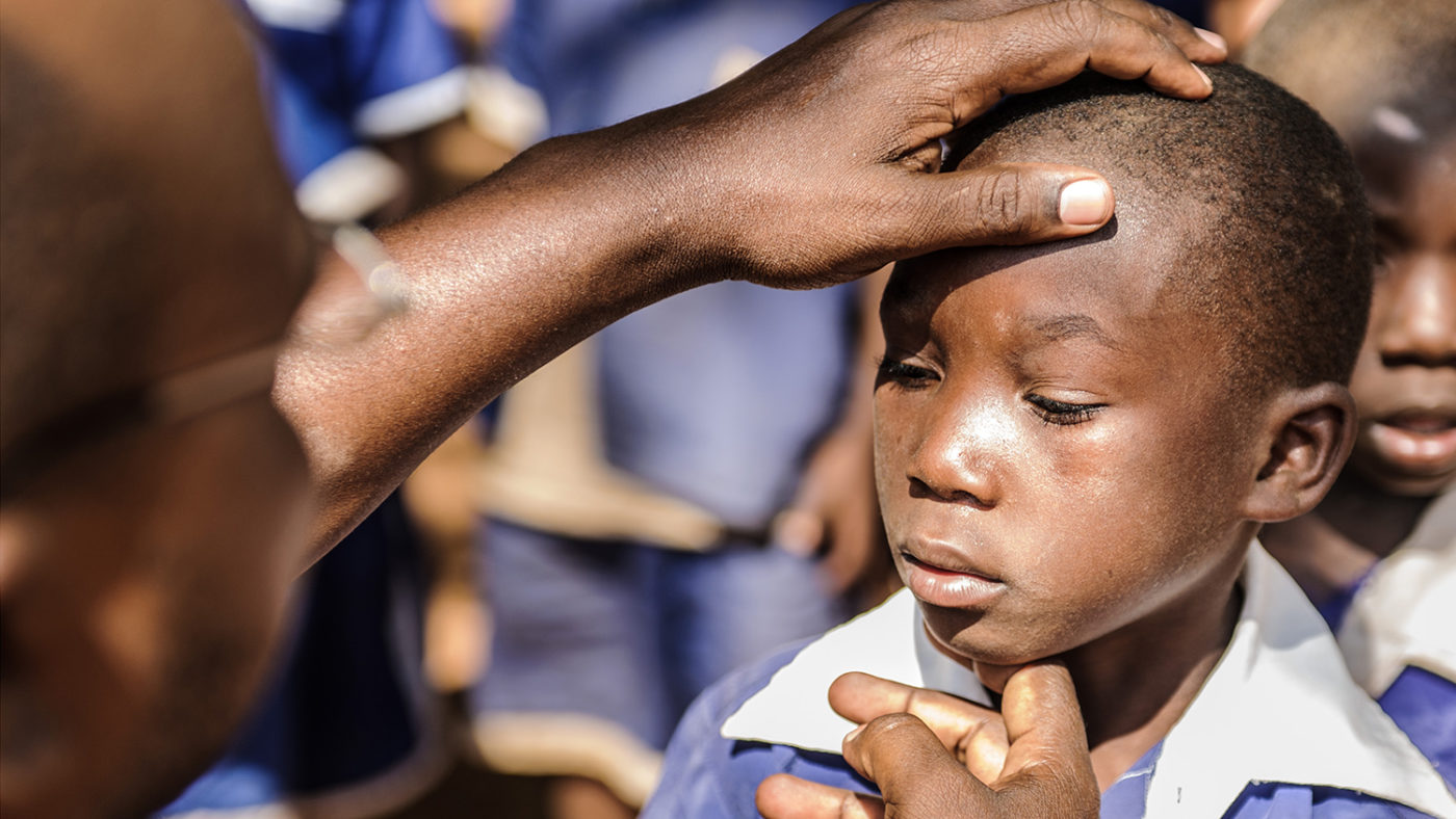 A young student has her eyes checked for trachoma.