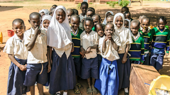 School children in Tanzania smile for the camera.