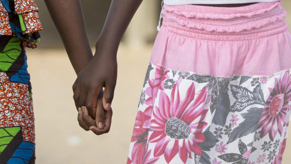 A close-up of two girls holding hands.