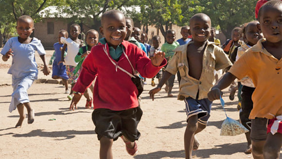 Young school pupils run in the playground, while smiling happily.